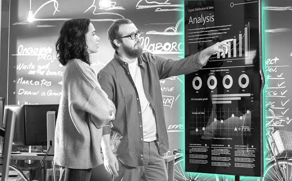 2 Menschen vor einem digitalen Display im Gespräch